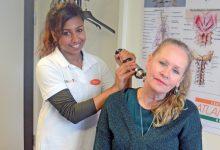 Linnea Holmkvist förbereder en behandling  av Gunilla Krafts onda rygg.